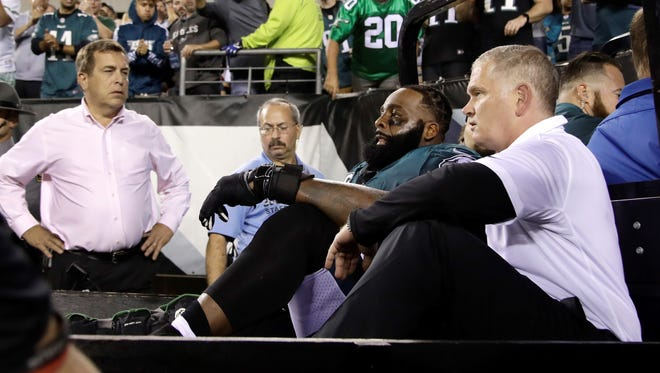 FILE - In this Monday, Oct. 23, 2017, file photo, fans cheer as Philadelphia Eagles offensive tackle Jason Peters, second from bottom right, is carted off the field during the second half of an NFL football game against the Washington Redskins in Philadelphia. Eagles coach Doug Pederson says Peters and starting linebacker Jordan Hicks will miss the rest of the season after being injured in Monday's 34-24 win over Washington.