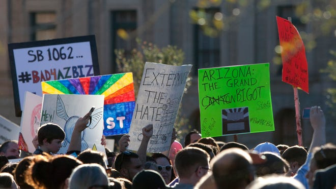 Activists protest at the state Capitol in Phoenix, Ariz., where Gov. Jan Brewer must decide by Saturday whether to sign, veto or let become law a bill that allows businesses to deny service to members of the LGBT community based on the religious beliefs of the business owner.
