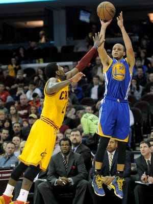 Golden State Warriors point guard Stephen Curry (30) shoots against Cleveland Cavaliers point guard Kyrie Irving (2) in the first quarter at Quicken Loans Arena.
