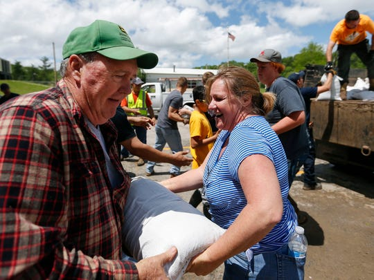 Volunteer Kimberly Griffin hands a sandbag to Marty