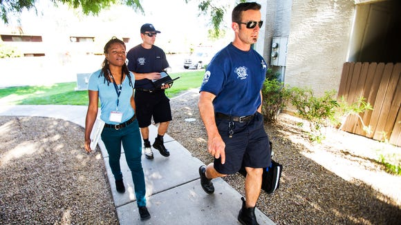 Ify Willson, a licensed behavioral health specialist with Crisis Preparation and Recovery, Inc. left, and Mesa Fire Captain Paramedics Rob Alkire, middle, and Brian Davy, approach an apartment in 2014 where a woman was reportedly hallucinating.  The team is part of a pilot program that may be adopted nationwide.