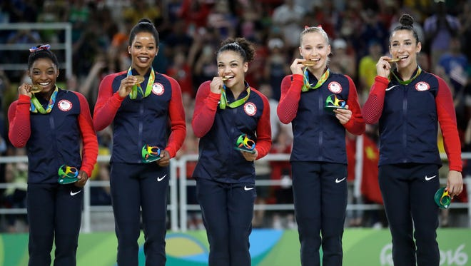 U.S. gymnasts, left to right, Simone Biles, Gabrielle Douglas, Lauren Hernandez, Madison Kocian and Aly Raisman hold their gold medals during the medal ceremony for the artistic gymnastics women's team at the 2016 Summer Olympics in Rio de Janeiro, Brazil, Tuesday, Aug. 9, 2016.