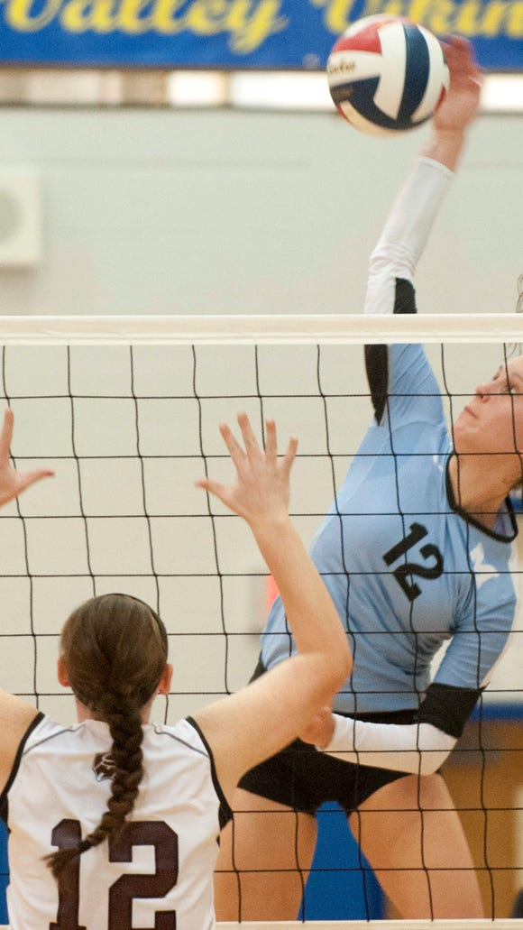 Mercy outside hitter Merideth Jewell smacks the ball toward Holy Cross opposite hitter Natalie Bodenbender. Mercy beat Holy Cross 3-0 to win the Sixth Region volleyball championship.