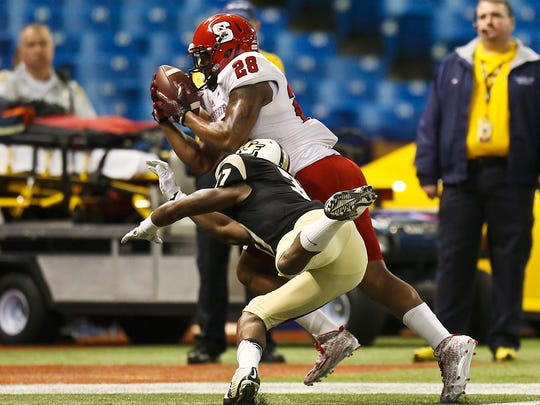 North Carolina State's Jaylen Samuels hauls in an 18-yard touchdown pass in front of UCF's Brandon Alexander in the first quarter during the Bitcoin St. Petersburg Bowl at Tropicana Field in St. Petersburg, Fla., on Friday, Dec. 26, 2014. (Jacob Langston/Orlando Sentinel/TNS)