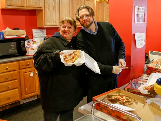 Rescue Mission Director Rich Bennett stands with a recipient of a pizza-seeking visitor on Wednesday afternoon.
