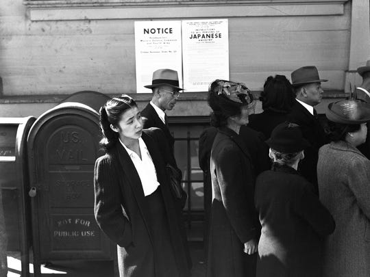 """Anxious residents on April 25, 1942, wait outside a """"civil control station"""" in San Francisco where they will be given instructions for their """"evacuation day."""" This photo is featured in an exhibit on Japanese internment at the FDR Presidential Library and Museum in Hyde Park."""