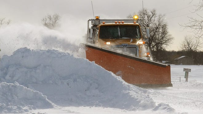 A St. Clair County Road Commission plow works during a heavy snowfall.