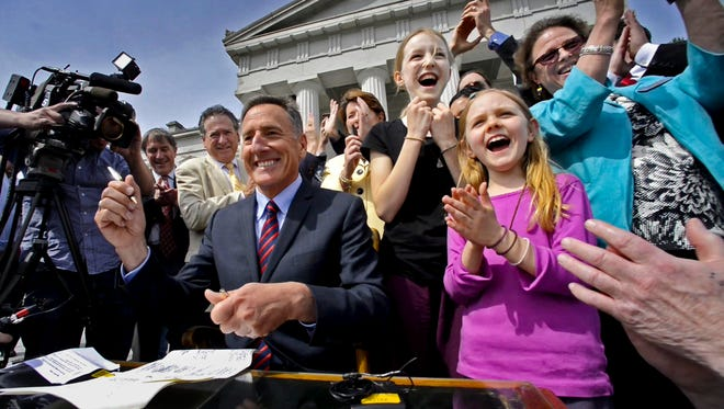 Vermont Gov. Peter Shumlin signs a bill requiring the labeling of food that contains genetically modified ingredients during a ceremony May 8, 2014, at the Statehouse in Montpelier, Vt. Standing next to him are sisters Brigid and Mollie Armbrust of West Hartford, Vt., who started a letter campaign to persuade legislators to pass such a law.