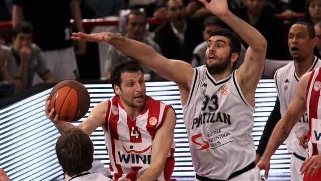 Slavko Vranes (cneter), guarding Olympiakos' Theodoros Papaloukas (second from left) while playing for Partizan Belgrade in May 2010, stands 7 feet 5 inches tall. The Montenegrin is one of the tallest NBA players ever.