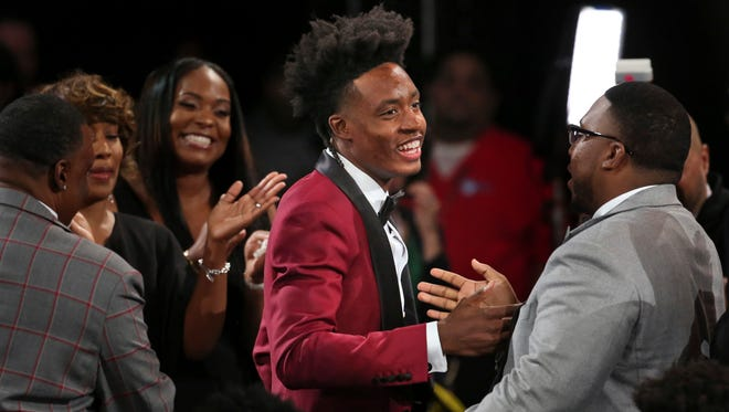Alabama's Collin Sexton is congratulated by friends and family after he was picked eighth overall by the Cleveland Cavaliers during the NBA basketball draft in New York, Thursday, June 21, 2018. (AP Photo/Kevin Hagen)