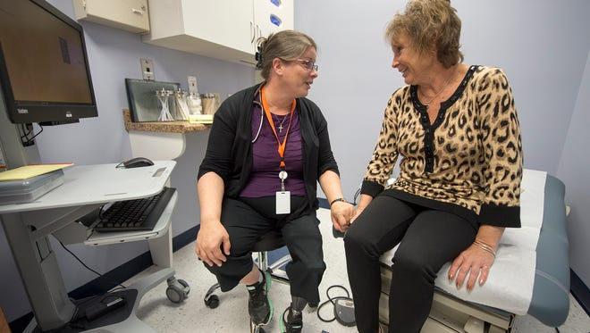 Dr. Marie Kellett, a family medicine physician, left, talks with patient Sue Flinchbaugh, of Mount Wolf, at Family First Health in Columbia.