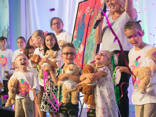 Leo and Lola Grabinski, center, and other patients from Golisano Childrens Hospital laugh as confetti flies at the Southwest Florida Wine & Food Fest on Saturday. Leo and Lola are the featured artists for this year's auction, and their artwork will be displayed in the new hospital.