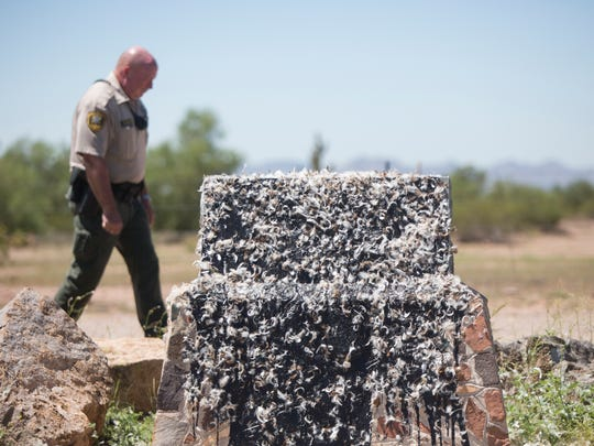 Pinal County Sheriff's Deputy Randy Palmer investigates the area around a memorial to the president of the Confederate States, Jefferson Davis, that sits tarred and feathered along State Route 80 outside Apache Junction on Aug. 17, 2017.