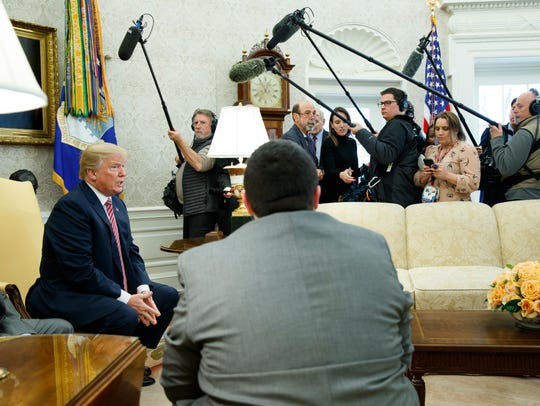 President Trump speaks to reporters in the Oval Office of the White House, Friday.