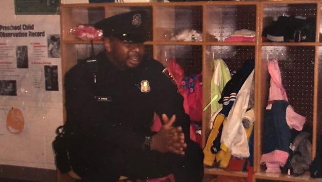 Detroit Police Officer Waldis Johnson speaks with metro Detroit schoolchildren in this undated photo.