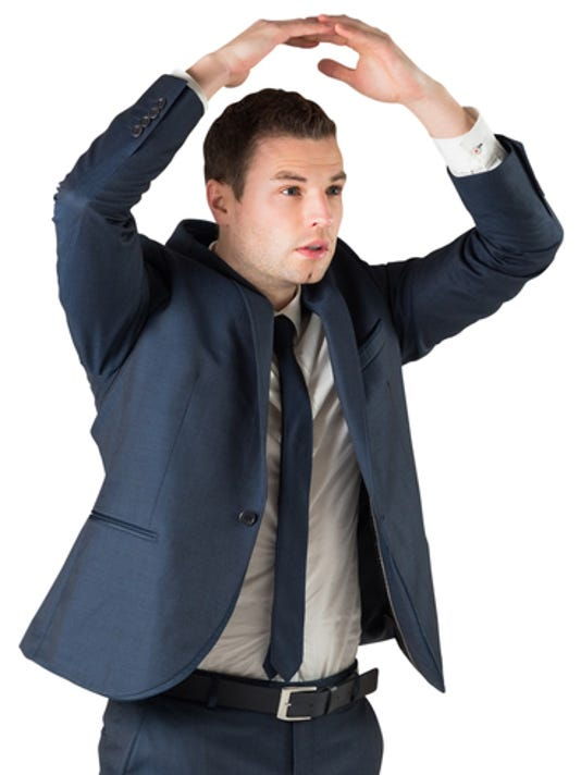 Businessman standing with hands over head