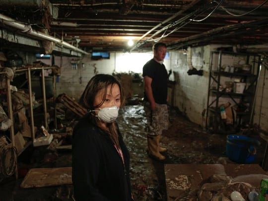 Theresa Chiang, 31, of Clinton Township in her basement on Wednesday Sept. 10, 2014, with her boyfriend Robert Baulch, 40, after the Aug. 11, 2014, rainstorm that damaged many homes throughout metro Detroit.