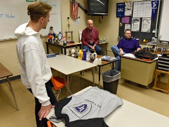 Jacob Waldock talks with his DECA advisors Mike Delaney,