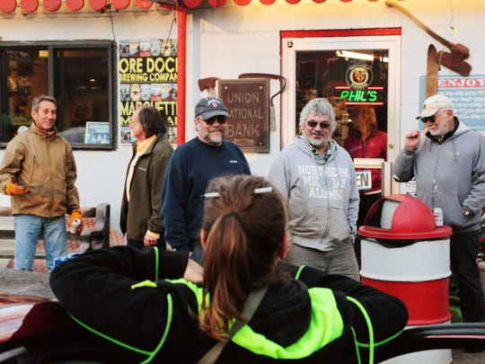 Phil Pearce (center right) and his friend Tom Buchkoe of Marquette talk with regulars enjoying beer outside Phil's 550 Store as the sun sets on Friday Nov. 11, 2016.