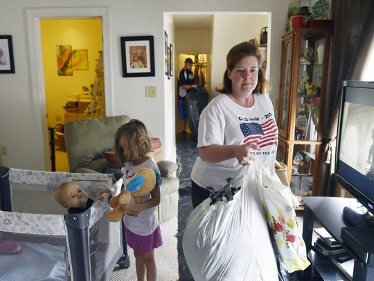 Amy Edwards moves items from her Red Lion attic to a truck as her 1-year-old grandson and 5-year-old granddaughter play Wednesday, June 7, 2017.