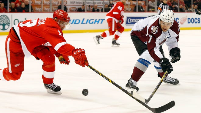 Detroit Red Wings center Pavel Datsyuk (13) and Colorado Avalanche center John Mitchell (7) battle for the puck during the first period of an NHL hockey game in Detroit Sunday.