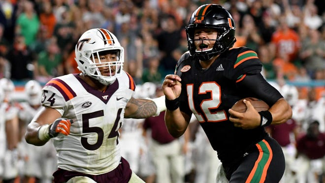Miami quarterback Malik Rosier runs in a touchdown past Virginia Tech linebacker Andrew Motuapuaka.