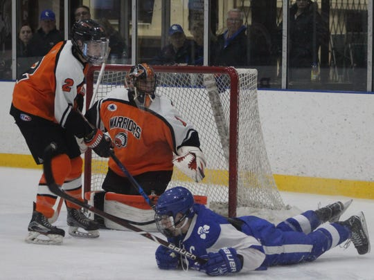 A Catholic Central player slides by Brother Rice goalie Pierce Cadieux and defender Ethan Nystrom.