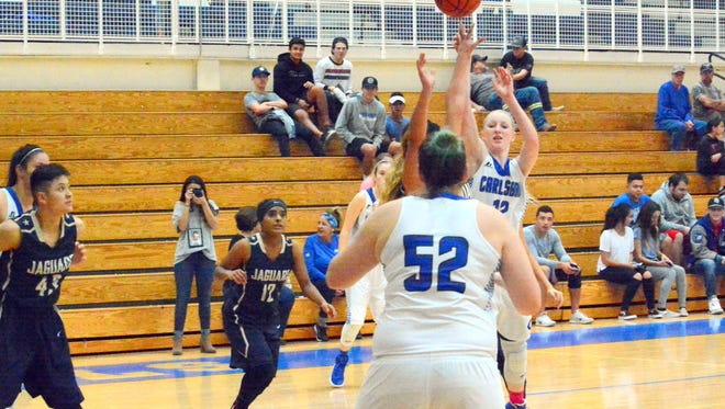 Carlsbad's Carsyn Boswell (12) passes the ball to teammate Teagan Rogers (52) on Saturday.