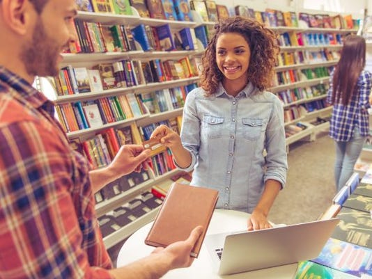 young woman with credit card at college bookstore