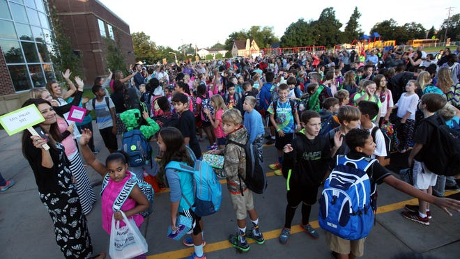 Children wave goodbye to their family members before the first day at Susan B. Anthony Elementary School last Tuesday.
