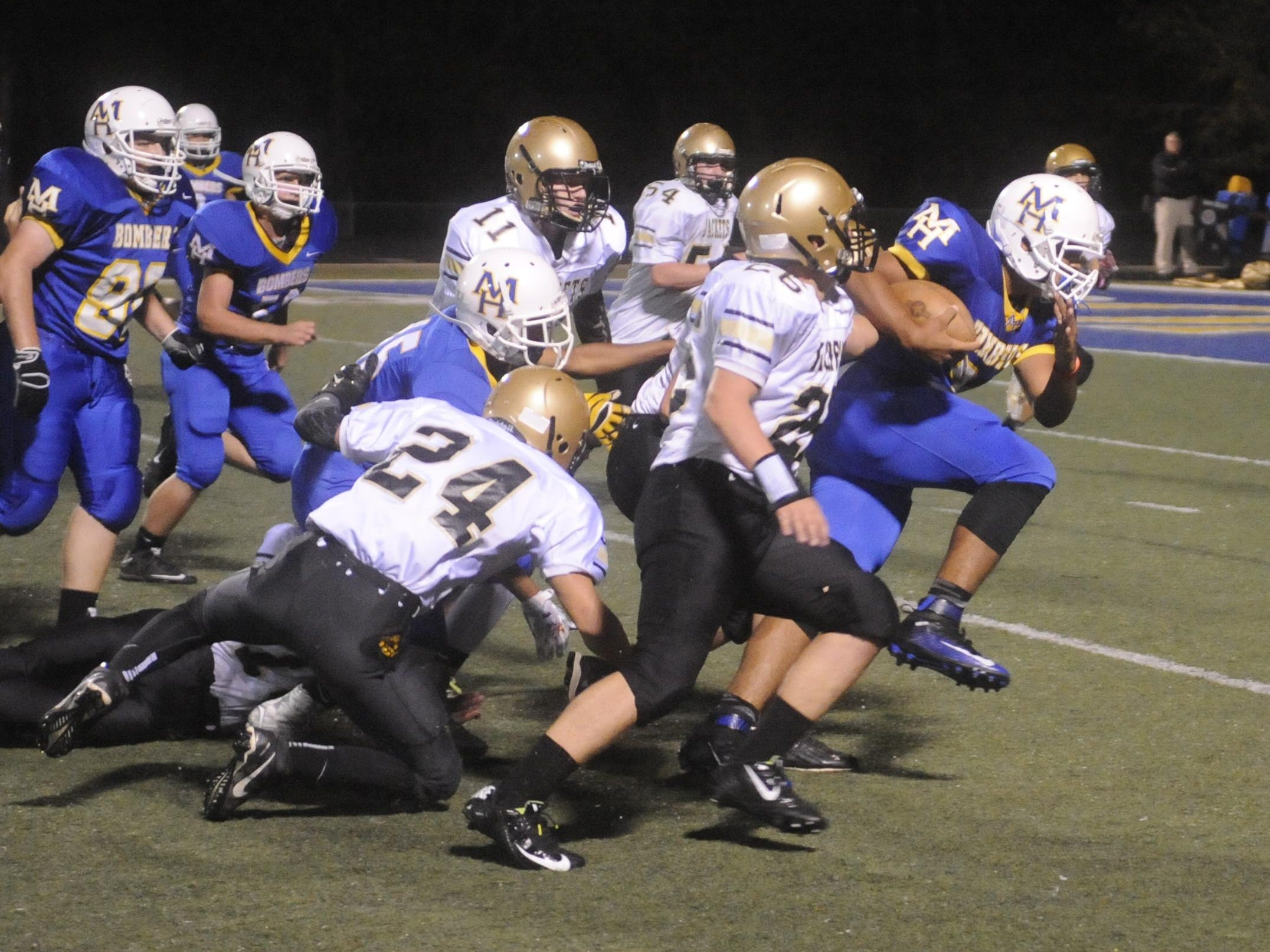 Mountain Home's Junior Williams, right, drags several Clinton defenders for a big gain during the Junior Bombers' 30-14 victory on Thursday night at Bomber Stadium. Williams rushed 22 times for 203 yards in the victory over the Yellowjackets.