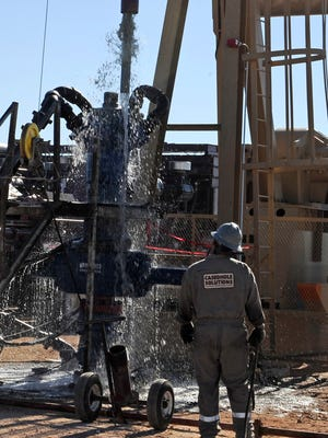 Water gushes out of a drilling pipe as it is pulled up to be replaced with a fresh pipe at a hydraulic fracturing site in Midland, Tex.