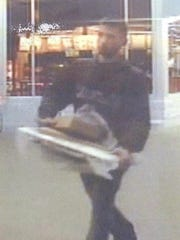 A suspect is pictured carrying a stolen laptop computer