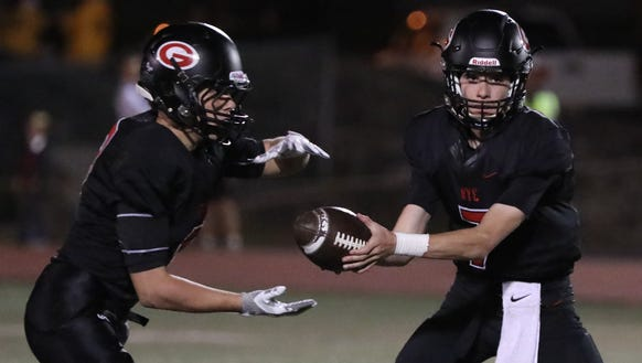 Rye quarterback Declan Lavelle hands off to Billy Chabot