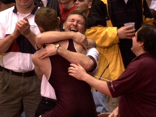 Dowling's Kelly Gray is hugged by Coach Ron Gray after