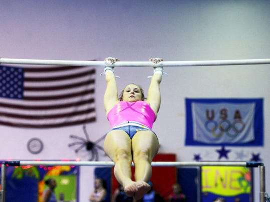 Sarah McCarty, 18, demonstrates a skill on the uneven bars during practice at Skyline Gymnastics Center in West Manchester Township on Wednesday. McCarty, who practices four hours a day, five days a week, is a Level 10 gymnast. Only a few hundred athletes in the country reach that level, which is a step below an elite Olympian.