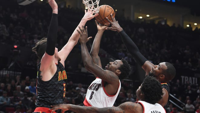 Portland Trail Blazers forward Al-Farouq Aminu drives to the basket on Atlanta Hawks forward Mike Muscala during the first half of an NBA basketball game in Portland.
