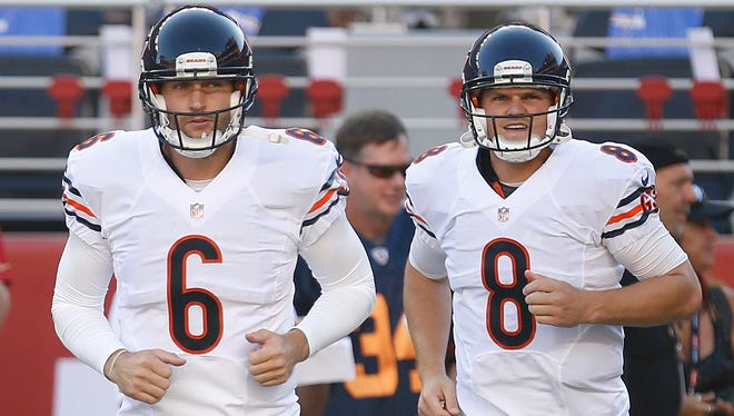 Chicago Bears quarterbacks Jay Cutler and Jimmy Clausen (8) run onto the field before a game against the San Francisco 49ers on Sept. 14, 2014.