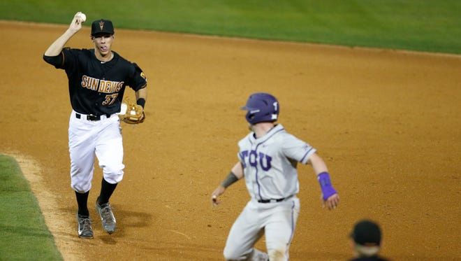 TCU catcher Evan Skoug avoids an out by shortstop Colby Woodmansee while a run scores during the eighth inning of a baseball game at Phoenix Municipal Stadium on February 20, 2015.