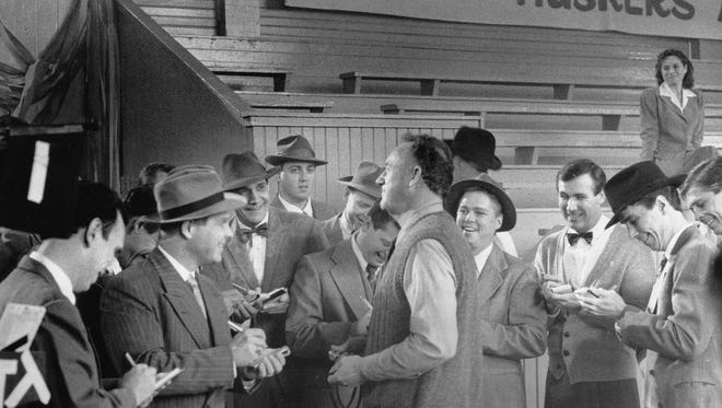 """Gene Hackman talks with """"newsmen"""" including Indianapolis Star reporter Scott Miley (center by wall) during filming of the movie Hoosiers in the gym in Knightstown on Nov. 2, 1985. About 20 actors and two real reporters portrayed early 1950s newsmen in the scene."""