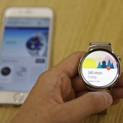 In this photo from Aug. 21, 2015, a new Android Wear smartwatch that is compatible with the Apple iPhone is displayed at Google's offices in San Francisco. Google is introducing an application that will connect Android smartwatches with Apple's iPhone, escalating the rivals' battle to strap their technology on people's wrists.