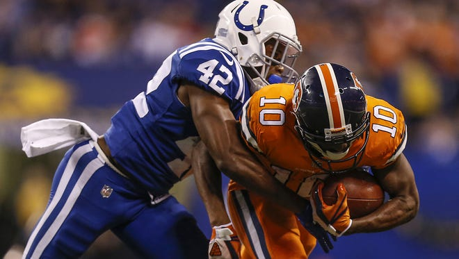 Indianapolis Colts defensive back Kenny Moore (42) tackles Denver Broncos wide receiver Emmanuel Sanders (10) after a first down gain at Lucas Oil Stadium in Indianapolis on Thursday, Dec. 14, 2017.