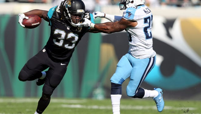 Jacksonville Jaguars running back Chris Ivory (33) makes a move to get around Tennessee Titans cornerback Brice McCain during the first half of an NFL football game, Saturday, Dec. 24, 2016, in Jacksonville, Fla. (AP Photo/Gary McCullough)