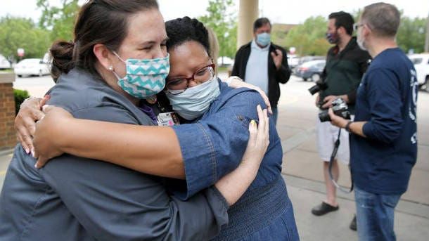 A Williamson Medical Center critical care nurse hugs India Scruggs, after Scruggs' partner Isaiah Whalum was released from the Franklin hospital on Feb. 12 after recovering from COVID-19.