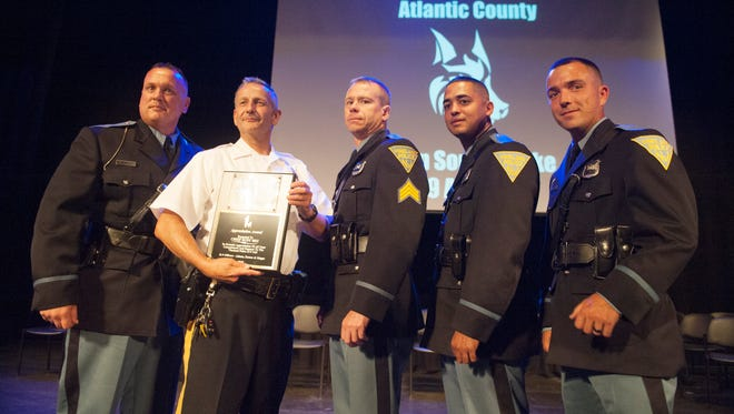"Vineland Police Chief Rudy Beu, 2nd from left, stands with (from far left), Vineland K-9 Officer Dwight Adams, Vineland Police Sgt. William Bontcue, Vineland K-9 Officer Johnathan Ramos, and Vineland K-9 Officer Derrick Magee after Chief Beu was issued an appreciation award from the Vineland K-9 officers following the Atlantic County Police Training Center John ""Sonny"" Burke K-9 Training Center Graduation Ceremony held at the Atlantic County Institute of Technology in Mays Landing on Friday, June 29, 2018."