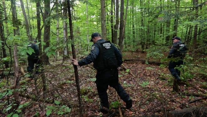 Members of the New York State Department of Corrections search a wooded area for two prisoners who escaped from the Clinton Correctional Facility on June 8 in Dannemora, New York.