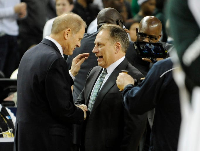 Michigan head coach John Beilein, left, greets MSU