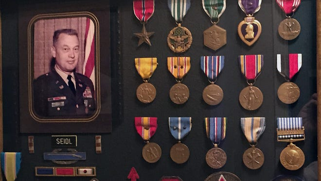 U.S. Army veteran Clarence Seidl is shown with the medals and patches he earned over his 28-year military career.
