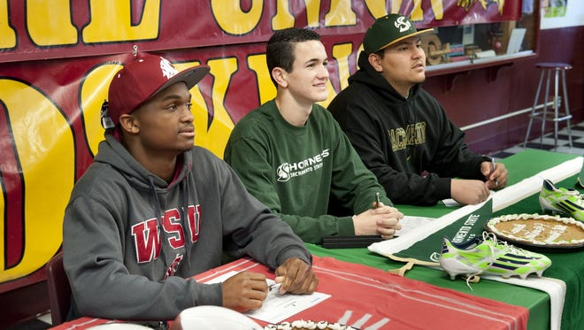 Tulare Union High School students Romello Harris, left, Christian Webb and Ulisis Nunez signed letters of intent on Wednesday. Harris plans to play football at Washington State, Webb will play soccer and Nunez will play football at Sacramneto State.