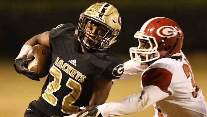 Greer's Dre Williams (22) springs free from Greenville's Reggie Norris during the Yellow Jackets' 48-15 win Friday night in a Class AAAA third-round playoff game at Dooley Field Friday night.
